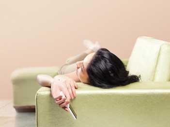 Woman laying on couch with remote in hand