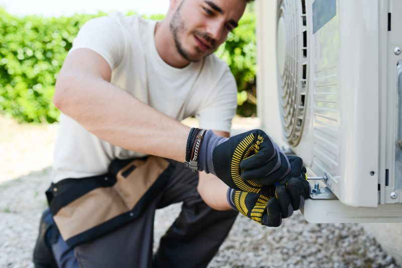 Employee installing air conditioning system