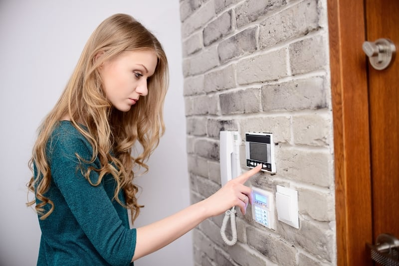Woman adjusting programmable thermostat