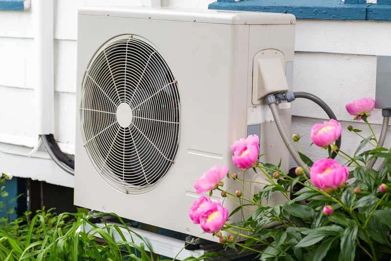 Heat pump unit installed to house surrounded by flowers