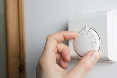 Woman controlling heat with thermostat