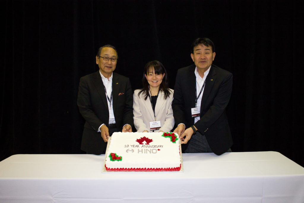 three people holding up a cake
